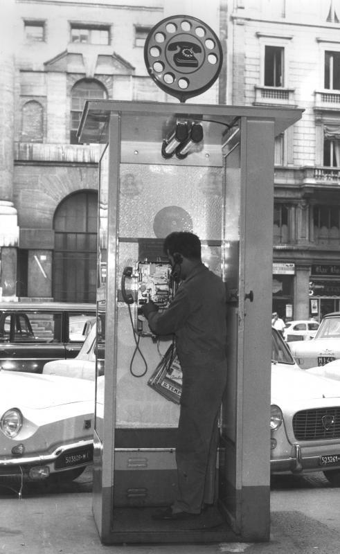 Milano, un tecnico riparatore verifica l'apparecchio a gettoni di una cabina stradale, 1961